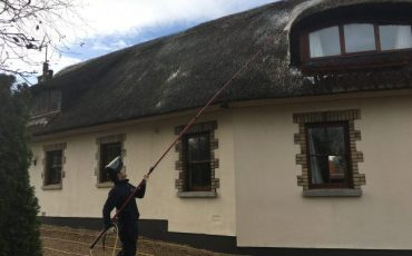 image of Thatched roof being cleaned of moss www.cleaning-service.uk.com